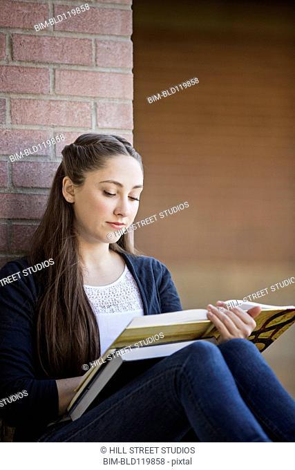 Caucasian student reading on campus