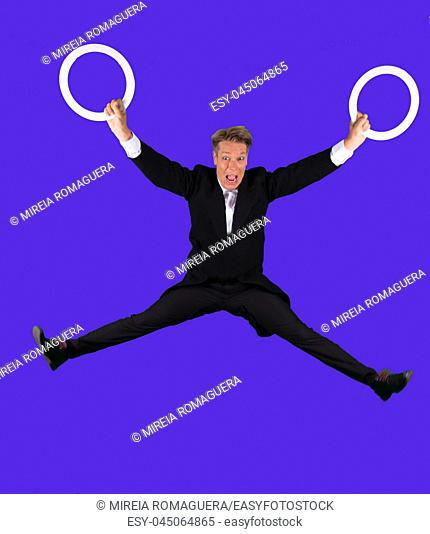 Elegant and scared juggler jumping with two juggling rings on his hands