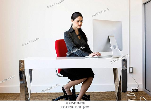 Young businesswoman sitting at desk, using computer