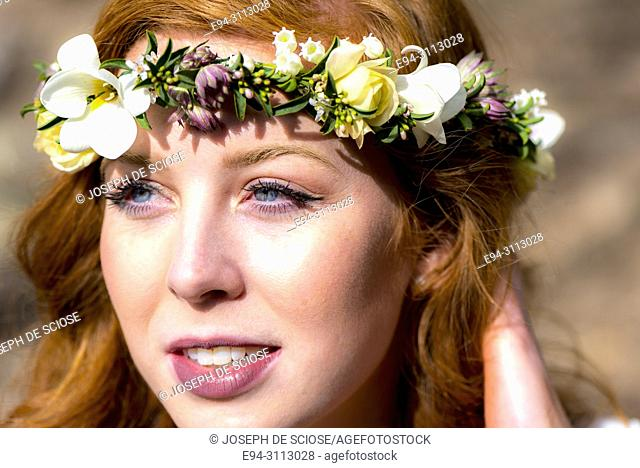 A portrait of a pretty 25 year old redheaded woman wearing a crown of flowers looking looking away from the camera