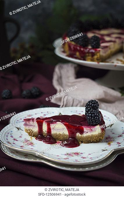 Slice of blackberry cheesecake on floral plate drizzled with blackberry sauce