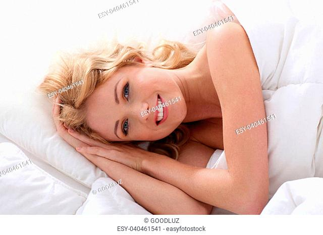 Beautiful smiling woman laying in bed