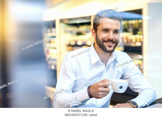 Smiling businessman with cup of coffee in a cafe