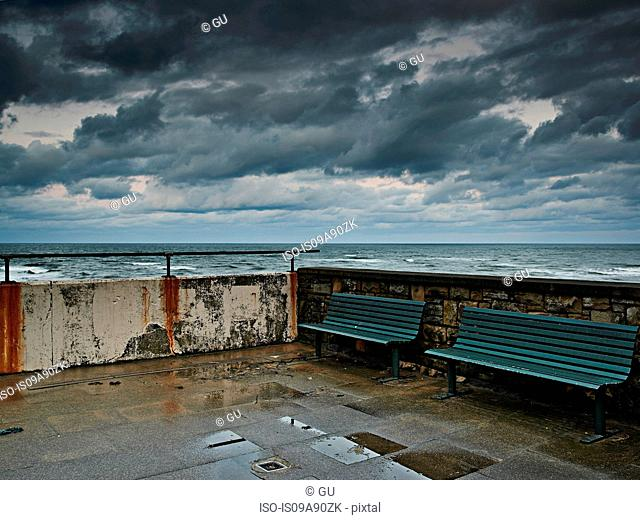 Two benches on end of pier on stormy day