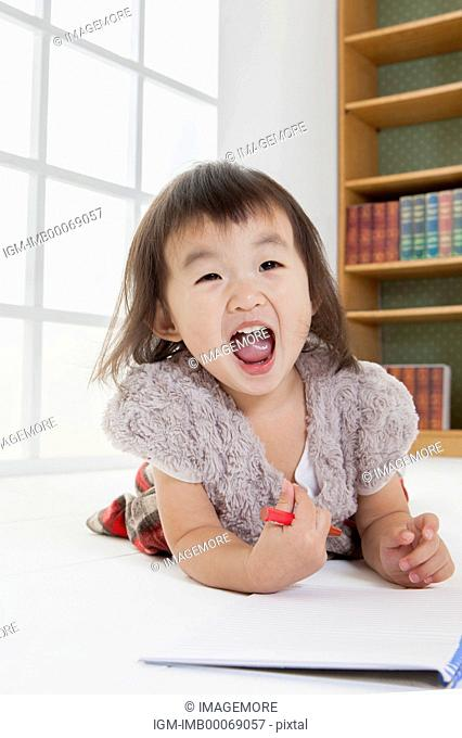 Little girl holding crayon and laughing