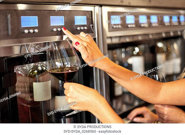 close up of woman with glass at wine dispenser