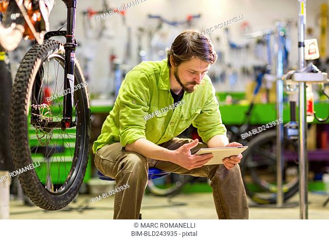 Caucasian worker using digital tablet in bicycle shop