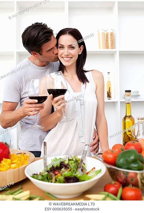 Lovers toasting with wine and cooking in the kitchen
