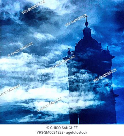 The reflection of a bell tower of the Cathedral of Puebla and a cloudy sky in a window in Puebla, Mexico