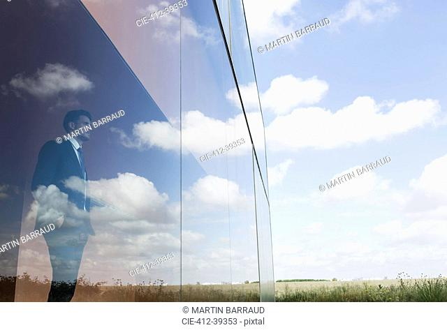 Pensive businessman looking out modern office window at blue sky and clouds