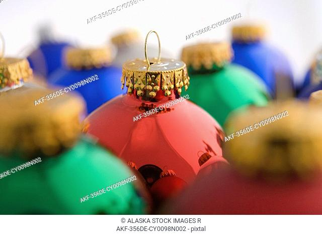Closeup of green Christmas tree bulb ornament stacked next to other colorful ornaments on white background studio portrait