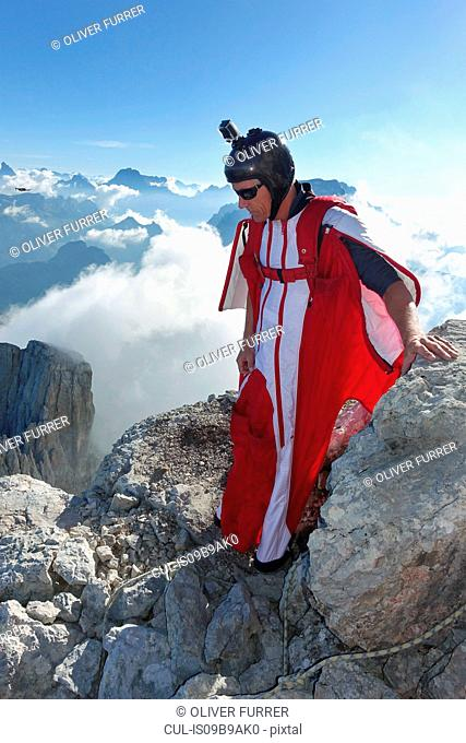 Male wingsuit BASE jumper preparing to fly from cliff edge