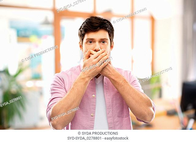 shocked man closing mouth by hands at office room