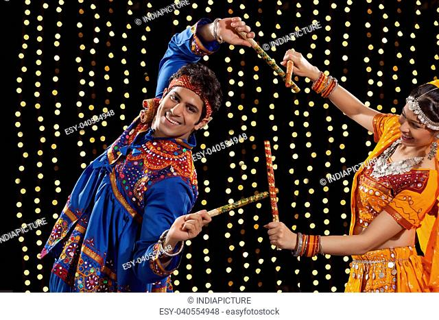 Portrait of young man performing Dandiya Rass with woman against neon lights