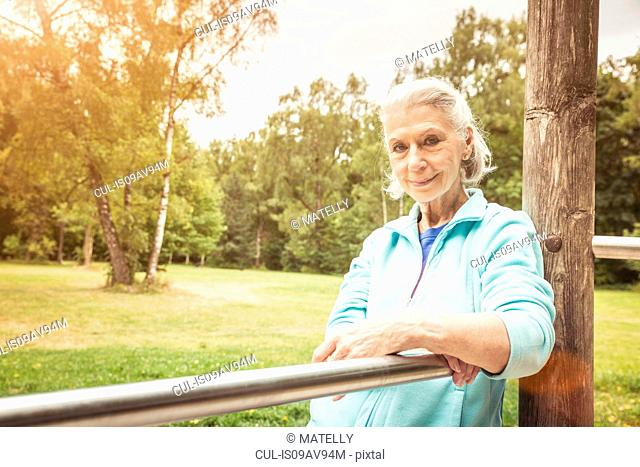 Portrait of senior woman leaning against metal bar in park looking at camera smiling
