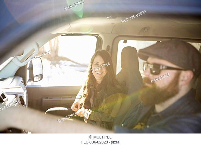 Young woman playing ukulele, riding in sunny van with boyfriend