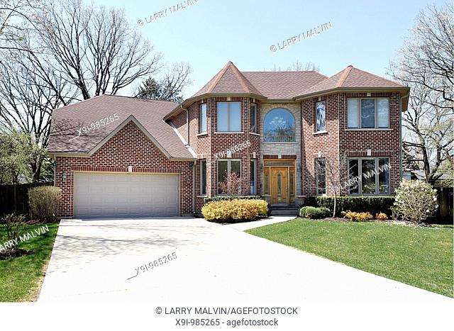 Luxury brick home in suburbs with stone entryway