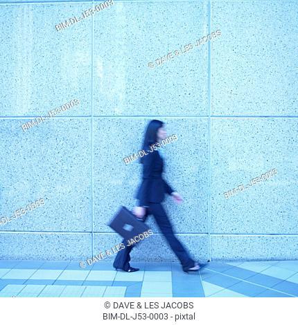 Blurred image of businesswoman walking