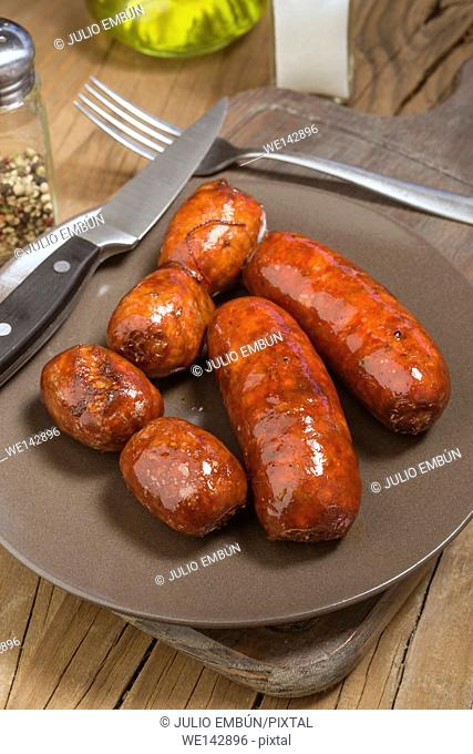 several Iberian sausages grilled in porcelain dish