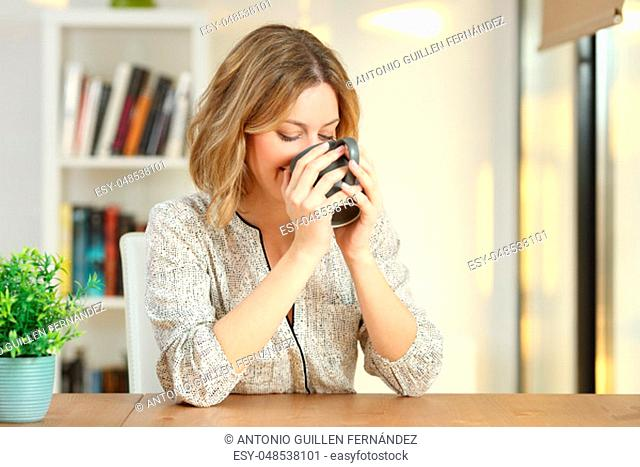 Happy woman drinking coffee from a mug on a table at home