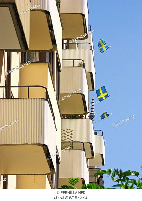 Scandinavia, Sweden, Stockholm, Swedish flags on balconies, low angle view