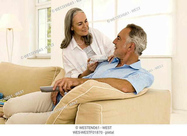 Mature couple in living room, smiling, close-up