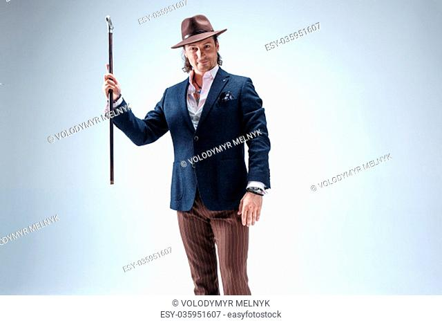 The mature man in a suit and hat holding cane. Isolated on a gray studio background