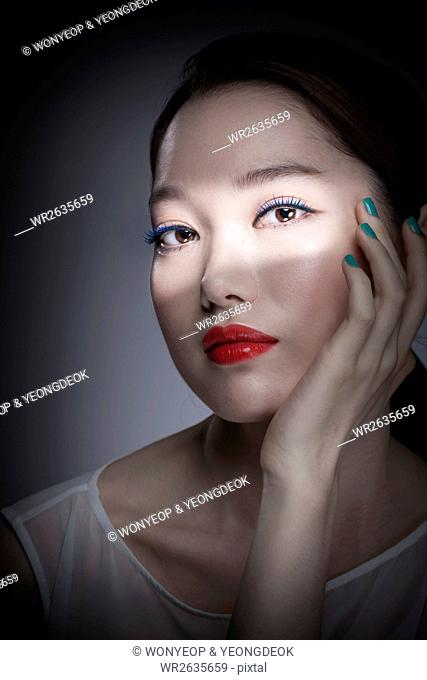 Portrait of young Korean woman with red lips and blue nails