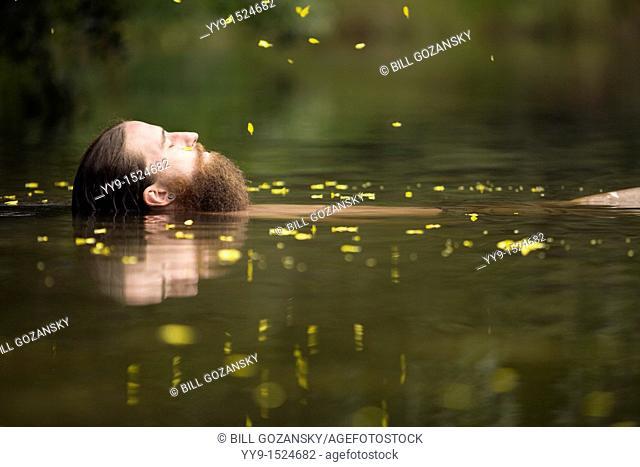 Man floating in lake - Cedar Mountain, North Carolina USA