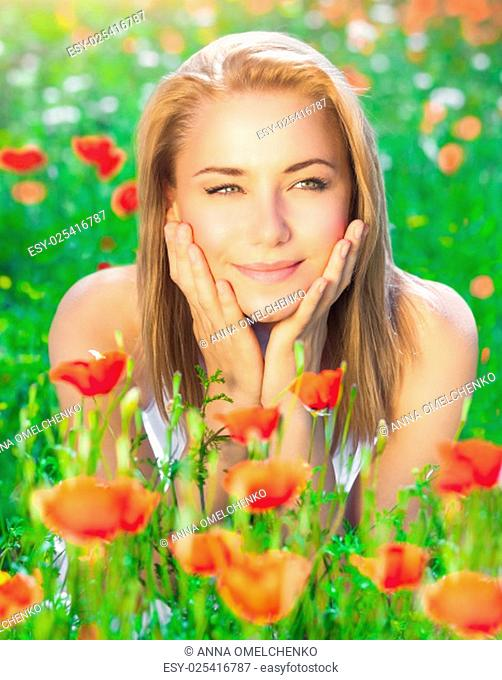 Beautiful woman lying down on fresh red poppy flowers field, enjoying beauty of countryside nature, relaxation and pleasure concept