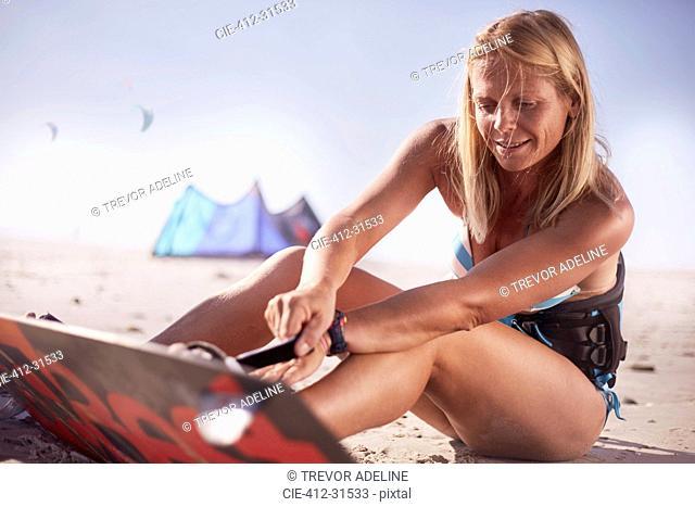 Woman fastening kiteboard to feet on sunny beach