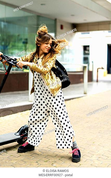 Portrait of smiling girl with E-Scooter wearing golden sequin jacket and polka dot jumpsuit tossing her hair