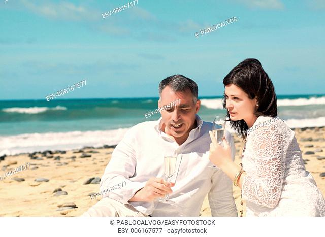 couples talking with glasses in hand on beach
