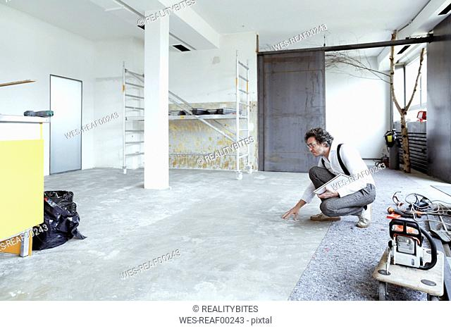 Architect checking screed at construction site