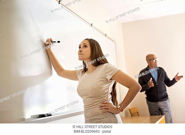 Teacher instructing student at whiteboard