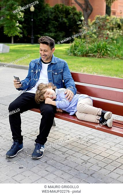 Happy father with son on a bench using cell phone and earbuds
