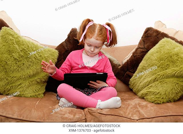 Little girl on a computer tablet, sat on sofa