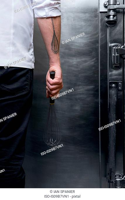 Cropped rear view shot of pastry chef with whisk tattoo holding whisk in kitchen