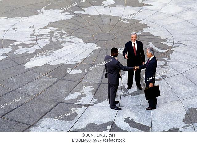 Businessmen shaking hands on map of globe