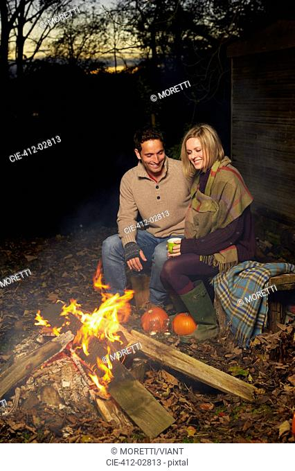 Couple talking around campfire at night