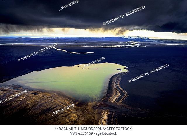 Ash clouds over a small lake with the Holuhraun Eruption in the background. August 29, 2014 a fissure eruption started in Holuhraun at the northern end of a...