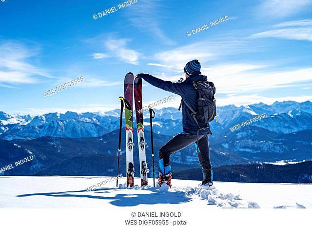 Germany, Bavaria, Brauneck, man on a ski tour in winter in the mountains having a break