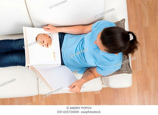 Young Woman On Sofa Looking At Baby's Photo At Home