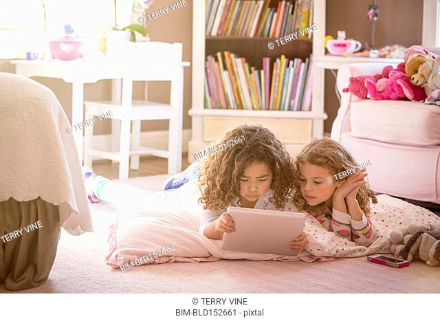 Girls using digital tablet on bedroom floor
