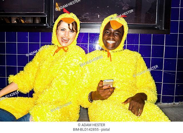 Couple wearing chicken costumes indoors
