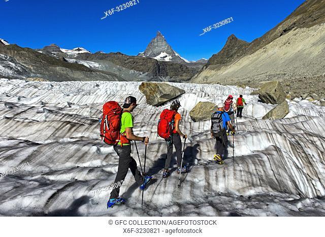 A group of alpinists on glacier trekking on the Gorner Glacier, peak Matterhorn behind, Zermatt, Valais, Switzerland