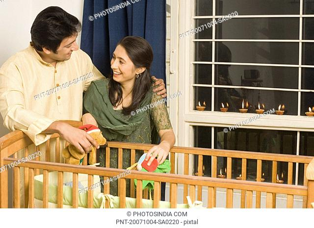 Mid adult man and a young woman smiling near a crib