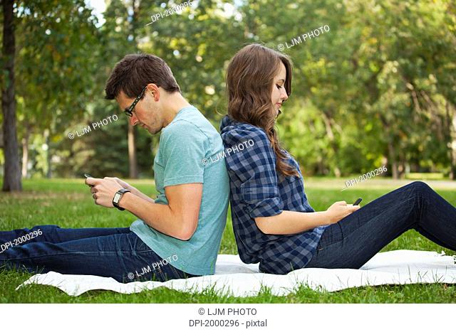 young couple looking at text messages on their phones as they sit back to back, edmonton alberta canada