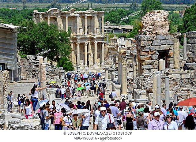 Large crowds view main street in Ephesus with Celsus library in background, Turkey
