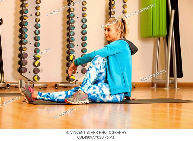 Woman in gym sitting on yoga mat looking away